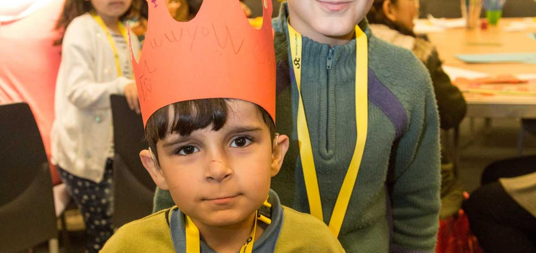 two boys standing, wearing crowns they have made