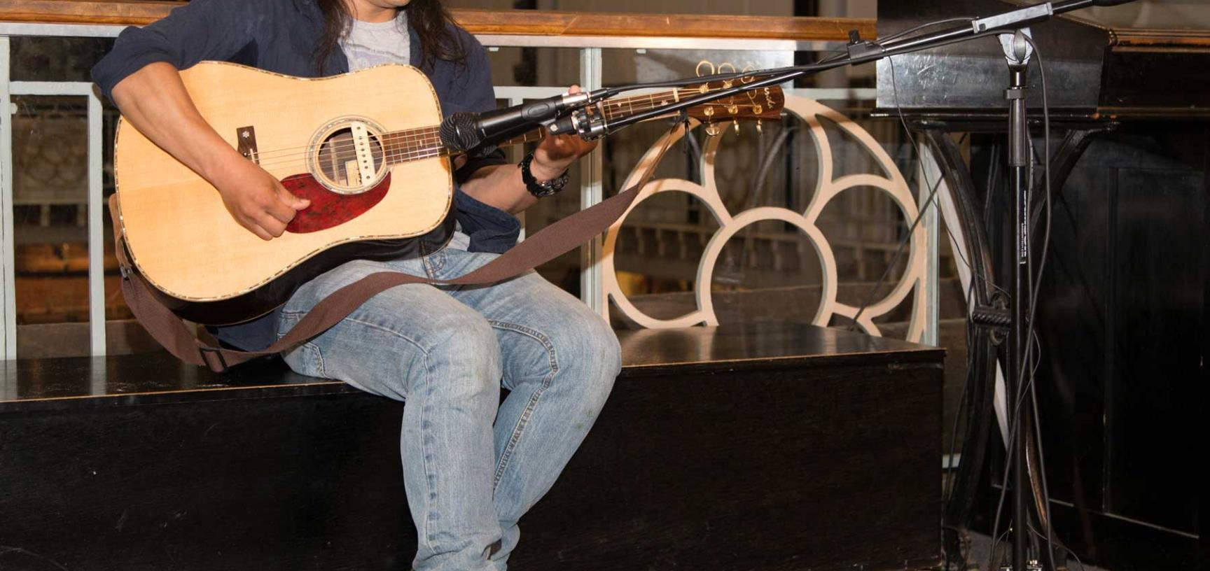 Gu Feng playing guitar at exhibition opening