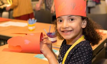 young girl smiling , making a crown at the family day