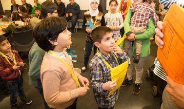 two boys looking up in a busy room