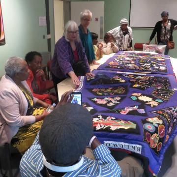 women sitting around a table, looking at the quilt they have made